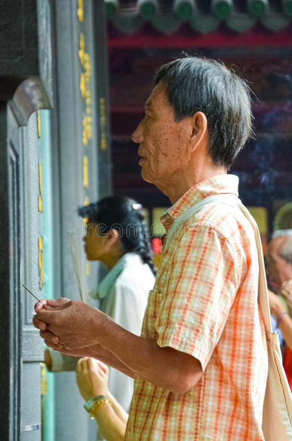 Taipei Taiwan - May 13th 2017: Old Asian man with prayer sticks praying in Longshan Temple. Religious ceremony, religion rituals. royalty free stock photos