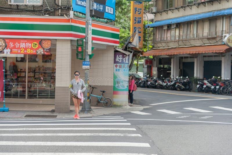 TAIPEI, TAIWAN - NOVEMBER 30, 2016: Taipei Street in one of suburb, district. Girl is Waiting Green Light. royalty free stock photos