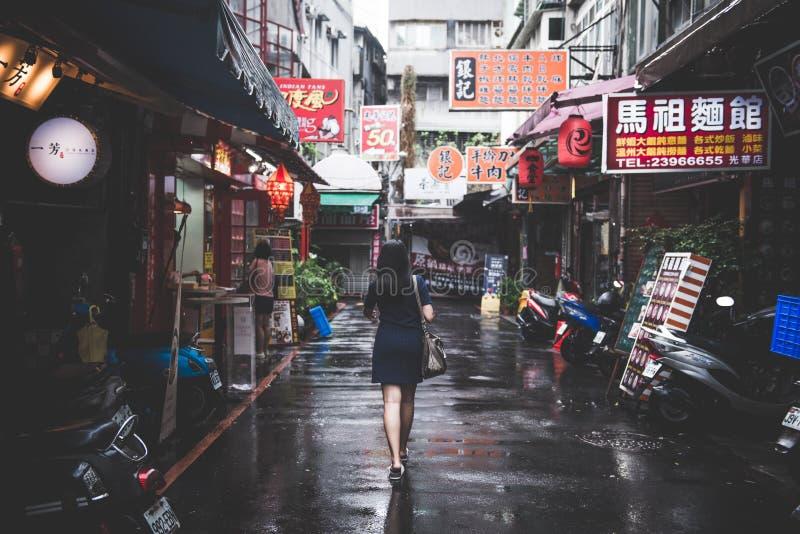 TAIPEI, TAIWAN - OUTUBRO 8,2017: Mulher dos viajantes que anda em ruas da cidade após chover fotografia de stock royalty free