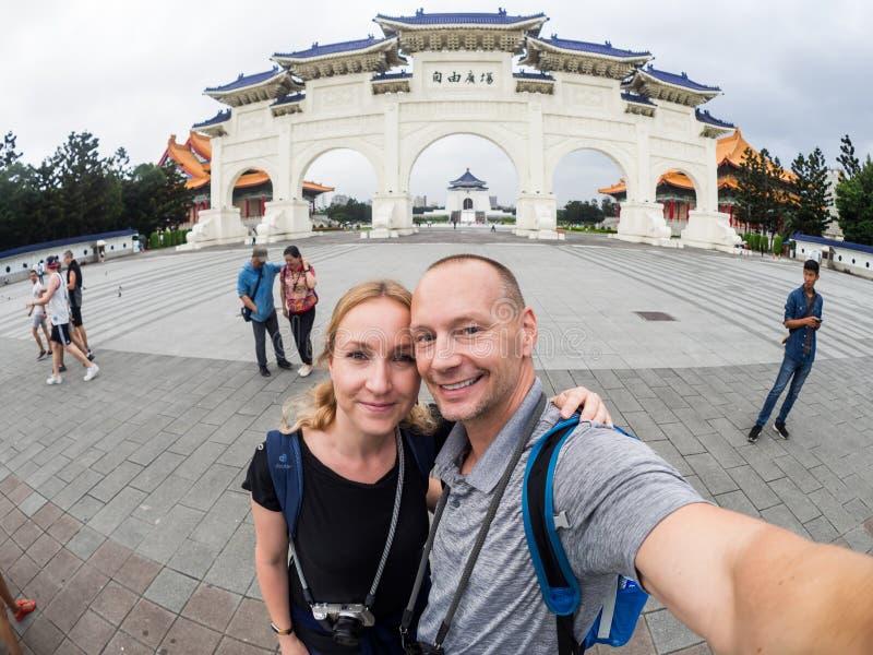 Taipei Taiwan - September 27, 2018: Det Caucasian paret gör selfie främst av Kai-kontrollen Memorial Hall royaltyfri foto