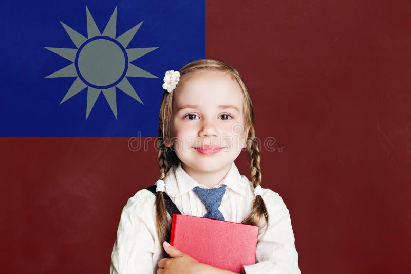 Taiwan begrepp med den lyckliga liten flickastudenten med boken mot den Taiwan flaggabakgrunden royaltyfri foto