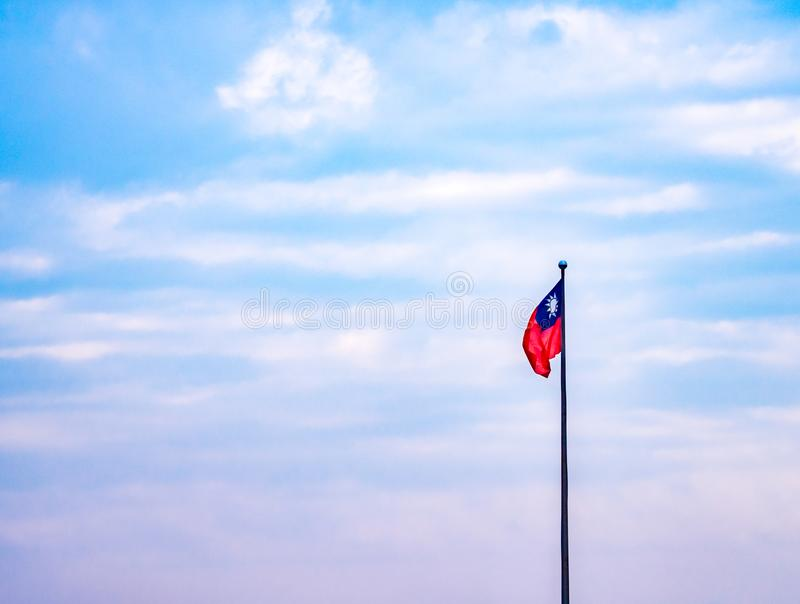 Taiwan nation flag waving on a pole with colorful pastel sky and clouds. stock image