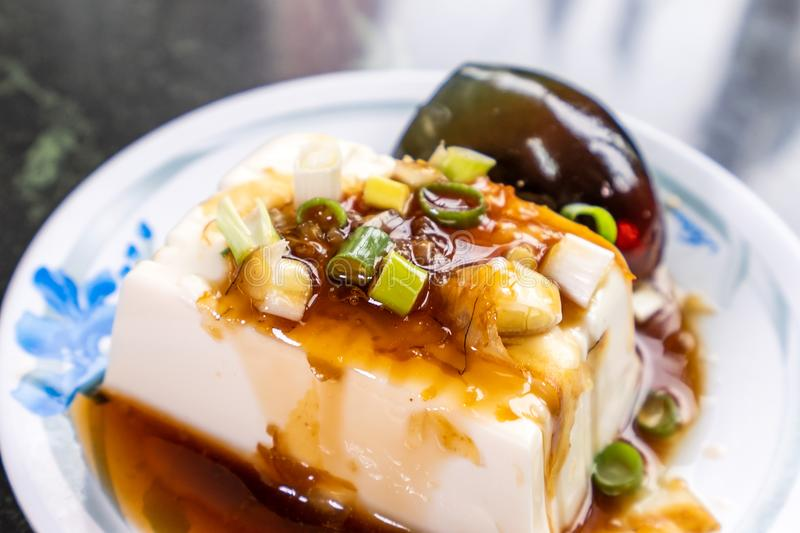 Taiwan`s distinctive famous snacks: thousand-year-old eggs tofupidan tofu in a white plate on stone table, Taiwan Delicacies stock photos