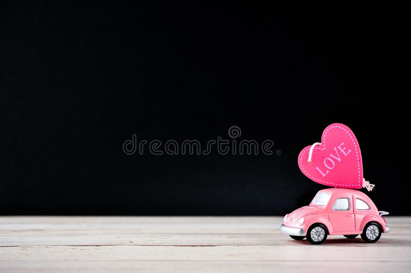 Taiwan, Tainan - April 17, 2018: Little beetle pink car carries a heart with love in blank background for text, Valentine`s Day co royalty free stock image