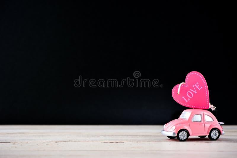 Taiwan, Tainan - April 17, 2018: Weinig kever roze auto draagt een hart met liefde op lege achtergrond voor tekst, mede de Dag va royalty-vrije stock afbeelding
