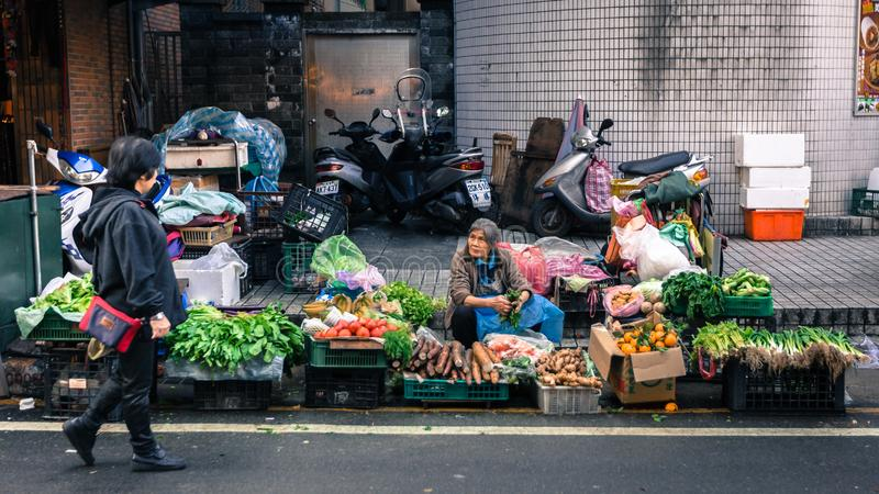 Poor old woman vendor sells vegetables on Taiwan street. TAIWAN, TAIPEI - FEBUARY 2014: An unidentified old woman vendor sells fresh fruits and vegetables at her stock images