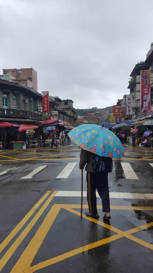 Taiwanesische ältere alte Frau trägt einen Regenschirm stockfotografie