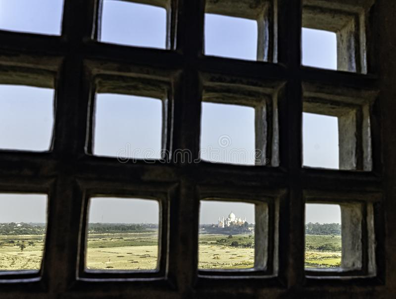 Taj Mahal behind bars - panoramic view of fields with Taj Mahal in background from Agra Red Fort royalty free stock images