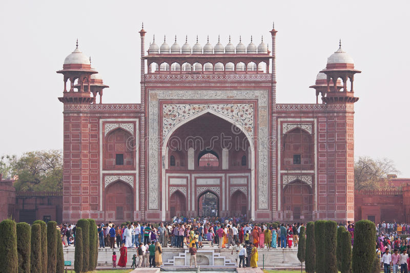 Taj Mahal Gateway. AGRA, INDIA - MARCH 23, 2014: View of visitors flocking through the main gateway to the Taj Mahal World Heritage site in the late afternoon in royalty free stock images