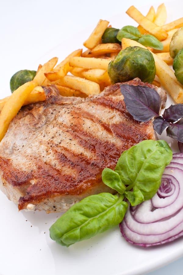 Tajadas de cerdo con las fritadas y las coles de Bruselas foto de archivo libre de regalías