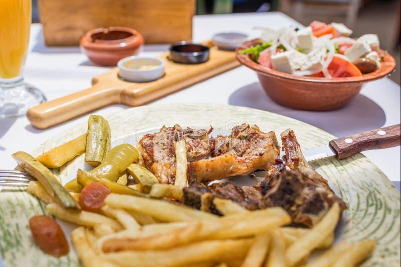 Tajadas de cordero con las verduras y las patatas de la carne asada en una placa en un restaurante o una taberna griego imágenes de archivo libres de regalías
