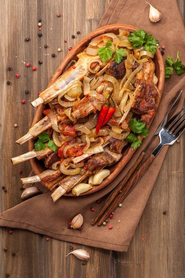 Tajadas de cordero fritas con las cebollas fritas, el ajo y las hierbas frescas foto de archivo libre de regalías