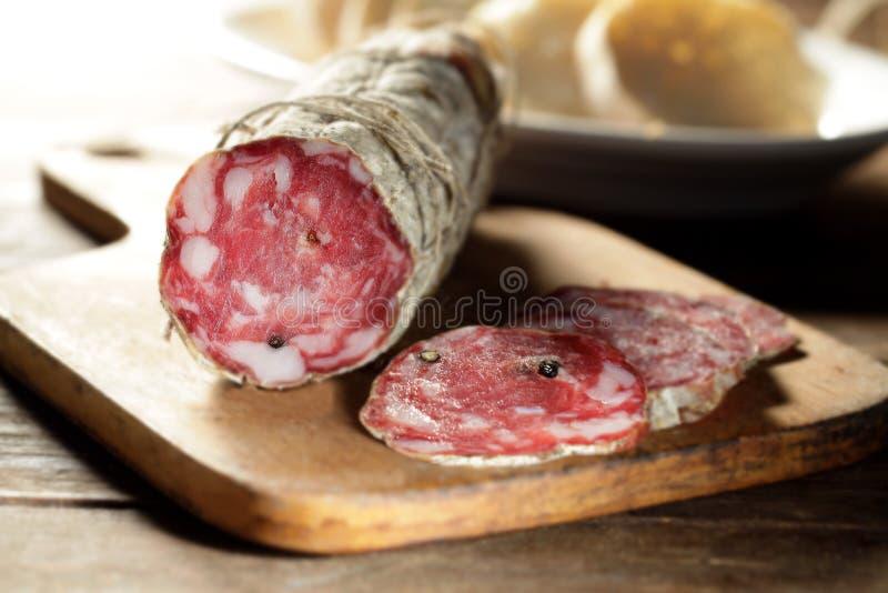 Tajadera con el salami cortado fotografía de archivo