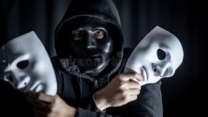 Tajemnica mężczyzna trzyma biel maski w czerni masce obrazy stock