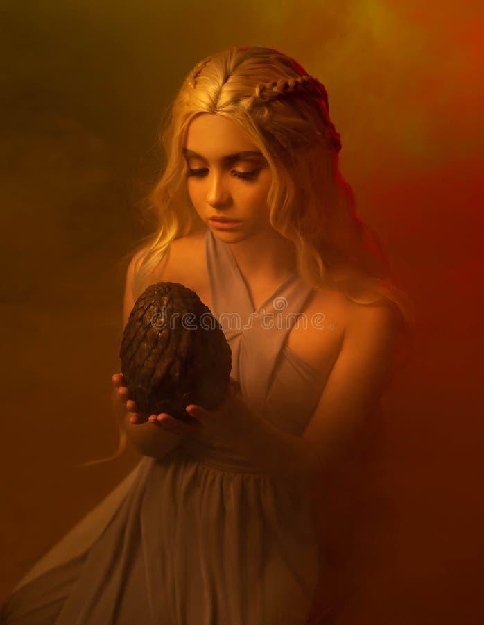 Tajemnicza dama z blondyn splatającym włosy siedzi w ciemnym pokoju w starej rocznik sukni, dziewczyna trzyma przerażać obraz stock