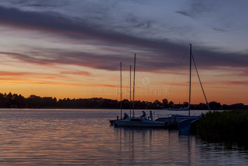 Tajemniczy krajobraz z żeglowanie łodziami po zmierzchu przy Kalwa jeziorem fotografia stock