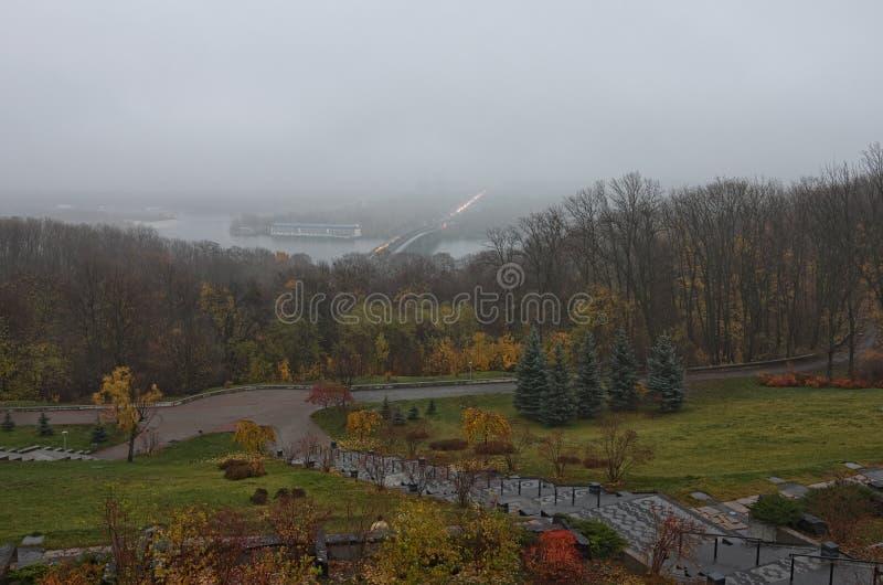 Tajemniczy mgłowy jesień ranek Panorama Kyiv od parka sława park chwała Metro most przez Dnipro rzekę obraz stock