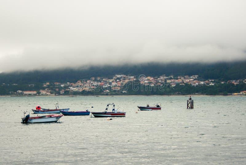 Tajemniczy morski miasteczko, łodzie i mgła, obraz royalty free