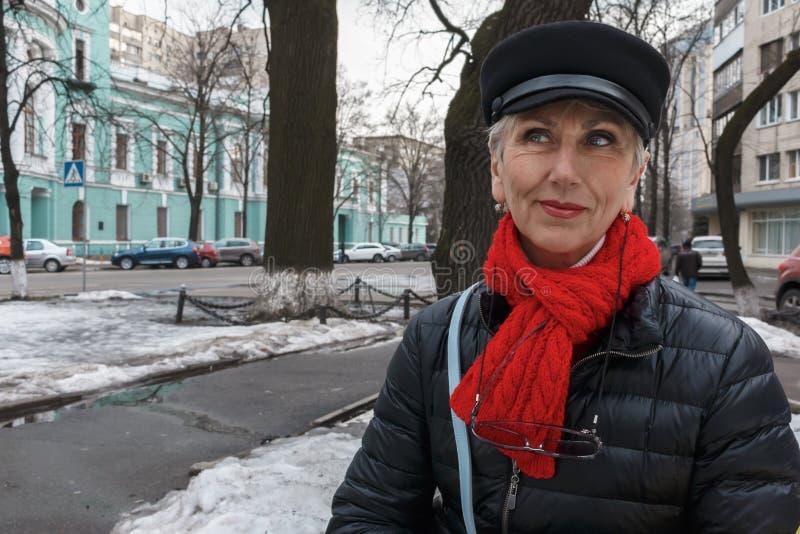 Tajemniczy smyle elegancka w średnim wieku kobieta w czerwonym szaliku i b zdjęcia royalty free