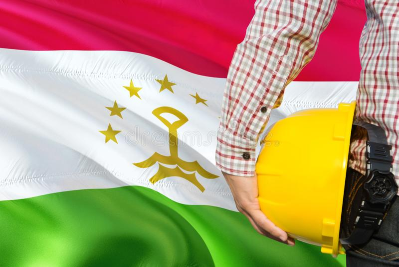 Tajik inżynier trzyma żółtego zbawczego hełm z machać Tajikistan chorągwianego tło Budowy i budynku poj?cie obrazy stock