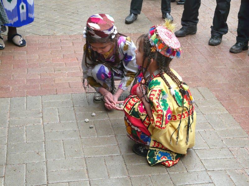 Tajik Mädchenspiel mit Kieseln lizenzfreie stockfotos