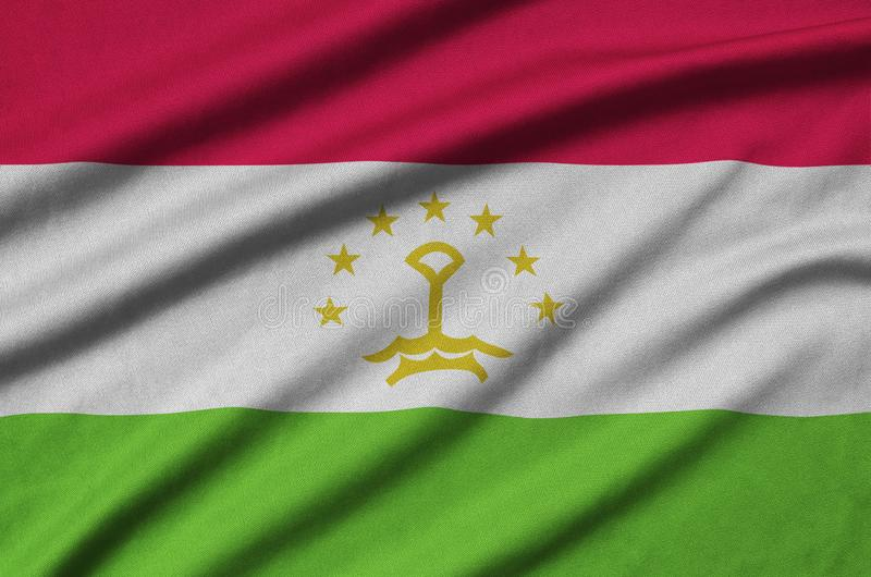 Tajikistan flag is depicted on a sports cloth fabric with many folds. Sport team banner stock photos