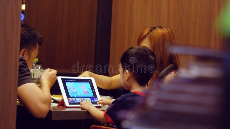Tajlandia, Bangkok, 23 2015 Listopad Azjatycki rodzinny łomotać w restauraci dziecko używa pastylkę zdjęcie royalty free