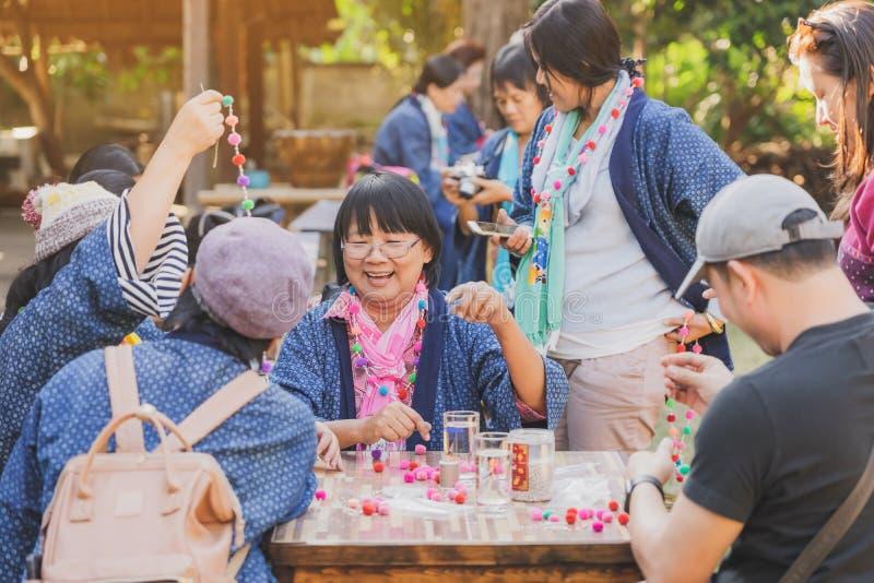 TAJLANDIA LAMPHUN - GRUDZIEŃ 12 R. : Niezidentyfikowane tajskie turystki uczą się robić naszyjnik z kuli przędzy 12 grudnia 2019 fotografia stock