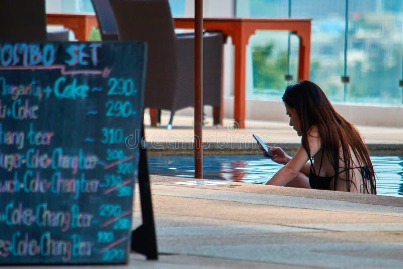 TAJLANDIA, PHUKET, MARZEC 19, 2018 - dziewczyna używa jej smartphone w basenie barem odosobniony tylni widok biel Pojęcie zależno obraz stock
