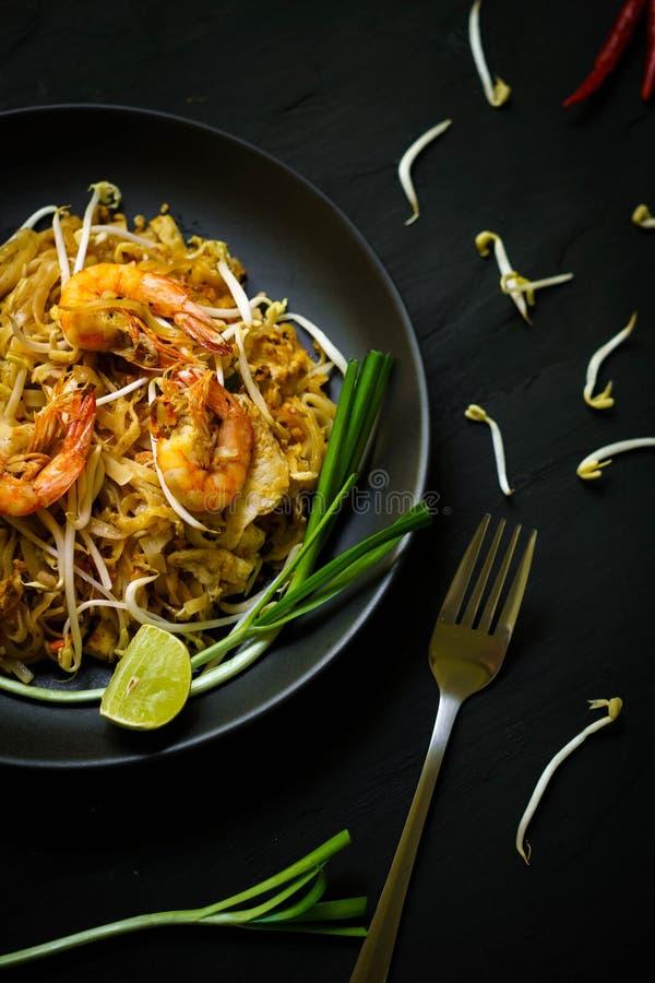 Tajlandia tradycyjna kuchnia, Mości smażących kluski, garneli i owoce morza tajlandzkiego, wysuszonego, uliczny jedzenie, ciemna  fotografia royalty free
