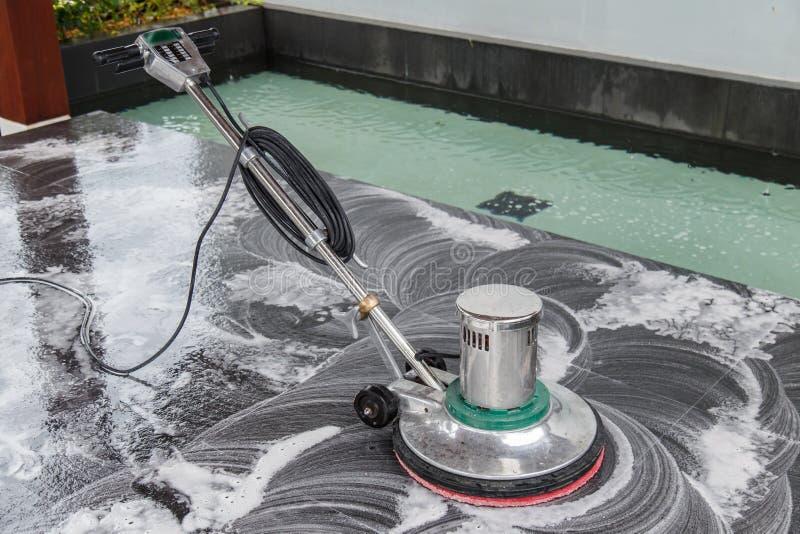 Tajlandzcy ludzie czyści czarnej granitowej podłoga z maszynowym i chemic fotografia stock
