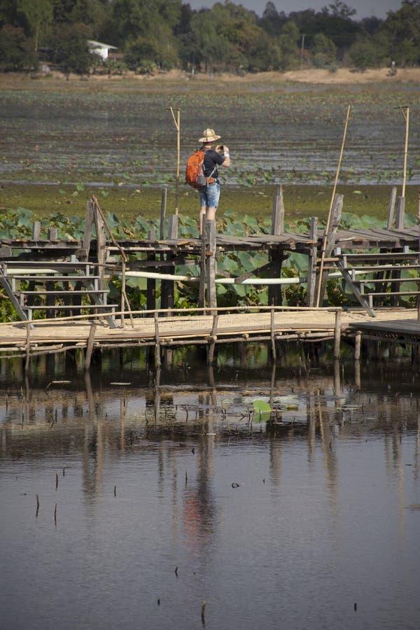 Tajlandzcy ludzie i obcokrajowów podróżnicy podróżują i chodzący wizytę na Kae tamy drewna moście długo przy Maha Sarakham, Tajla zdjęcie royalty free