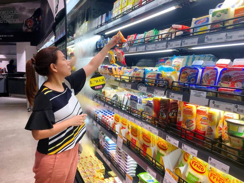 Tajlandzka kobieta wybiera niektóre serowego masło w fridge przygotowywającym obrazy stock
