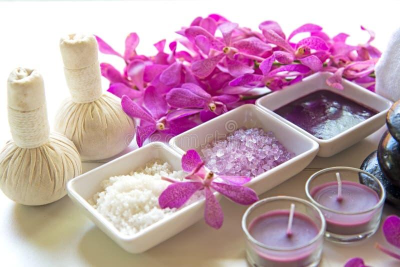 Tajlandzka zdrojów traktowań aromata terapii sól i cukrowy masaż z storczykowym kwiatem na drewnianym bielu pętaczki i rockowego  obraz royalty free