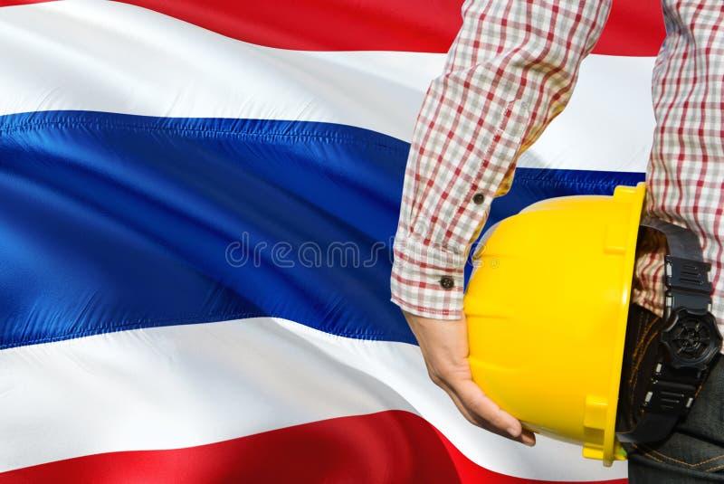 Tajlandzki inżynier trzyma żółtego zbawczego hełm z machać Tajlandia chorągwianego tło Budowy i budynku poj?cie zdjęcia stock