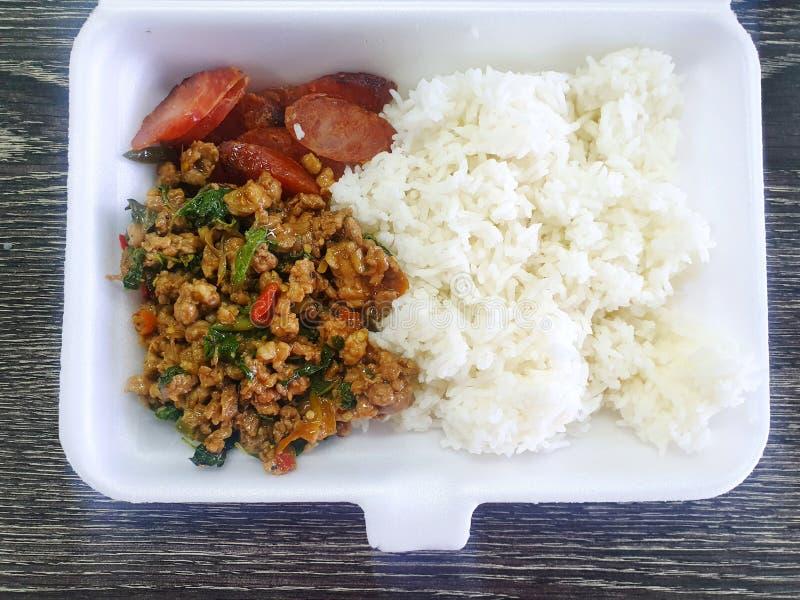 Tajlandzki jedzenie styl, Rice nakrywał z fertanie smażącą minced wieprzowiną z świętymi basilów liśćmi i smażącą kiełbasą w pian obrazy stock