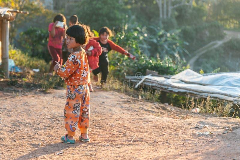 Tajlandzki p??nocny dzieciak jest ubranym pyjamas stoi z ?wiat?em s?onecznym i jej przyjaci??mi w tle w Akha wiosce Maejantai zdjęcia royalty free