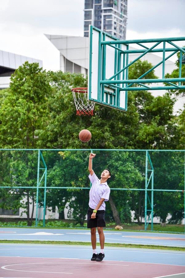 Tajlandzki uczeń robi layup krótkopędu boisko do koszykówki publicznie obrazy royalty free