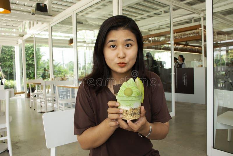Tajlandzkiego kobiety przedstawienia melonowy lody przed jeść przy kawiarnią obrazy stock