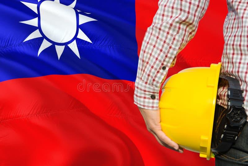 Tajwański inżynier trzyma żółtego zbawczego hełm z machać Tajwan chorągwianego tło Budowy i budynku poj?cie fotografia royalty free