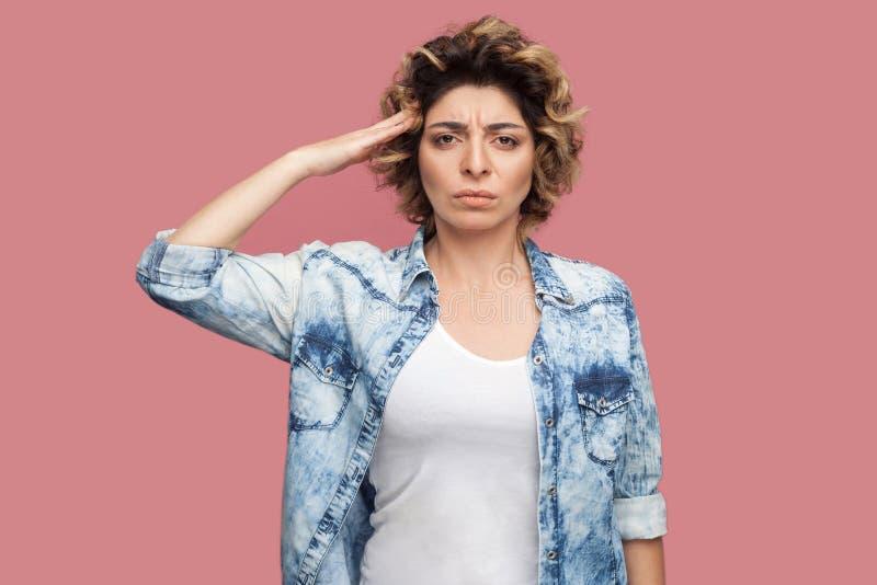 Tak sir Portret poważna młodego pracownika kobieta z kędzierzawą fryzurą w przypadkowej błękitnej koszulowej pozycji i patrzeć ka obrazy royalty free