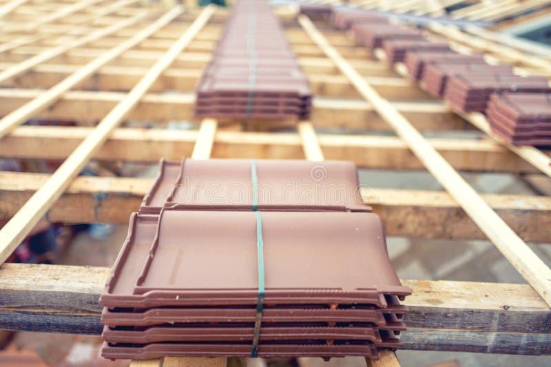 Tak under konstruktion med buntar av bruna taktegelplattor som är förberedda på trästrukturen royaltyfria bilder