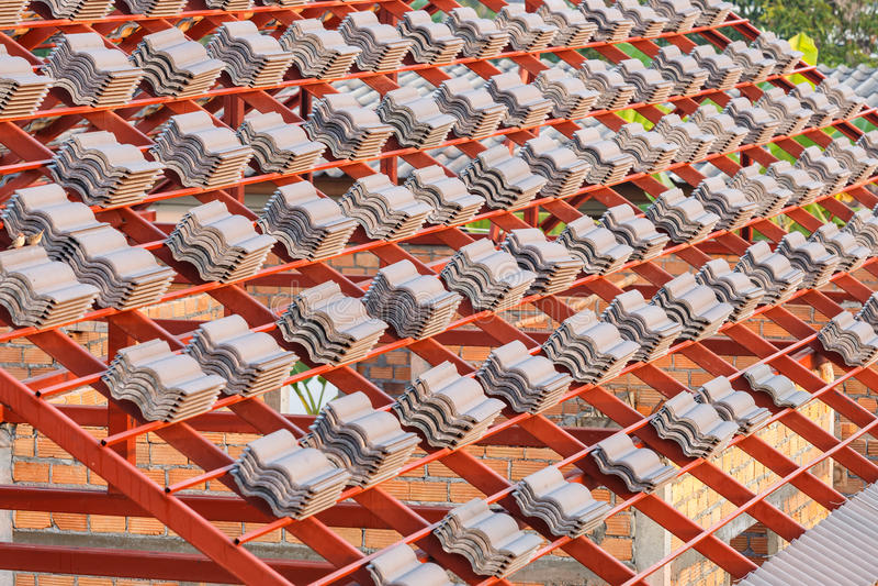 Tak under konstruktion med buntar av taktegelplattor för hem- byggande arkivbilder