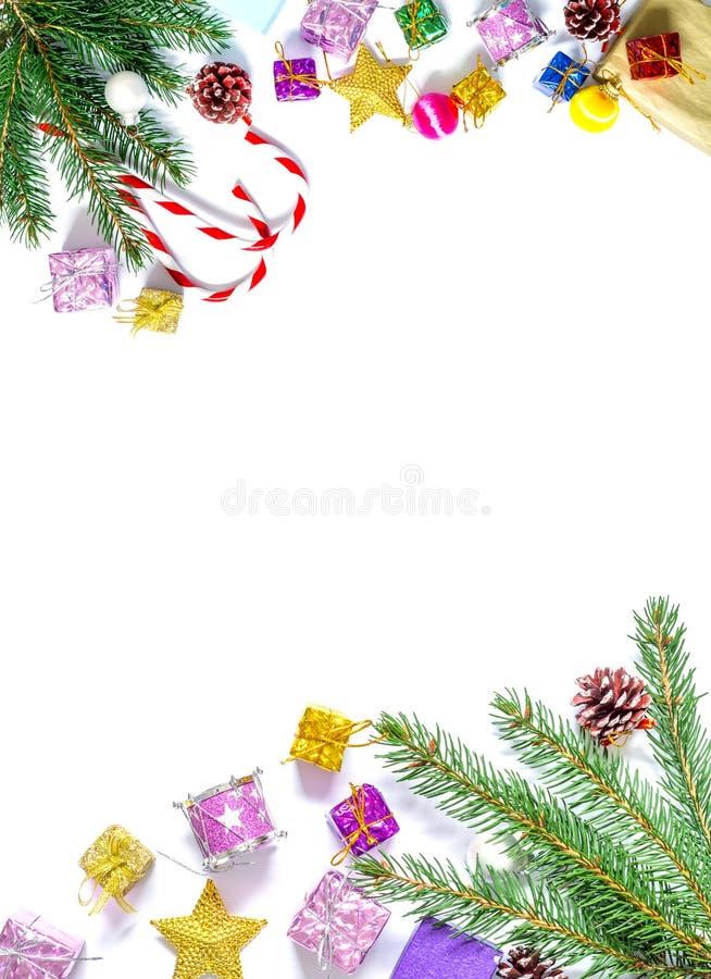 Tak van een Kerstboom met ballen, sparappel, traditionele die suikergoed en dozen met giften op een witte achtergrond worden geïs stock foto's