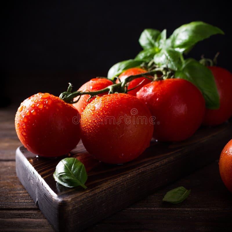 Tak van rijpe natuurlijke tomaten en basilicumbladeren stock afbeeldingen