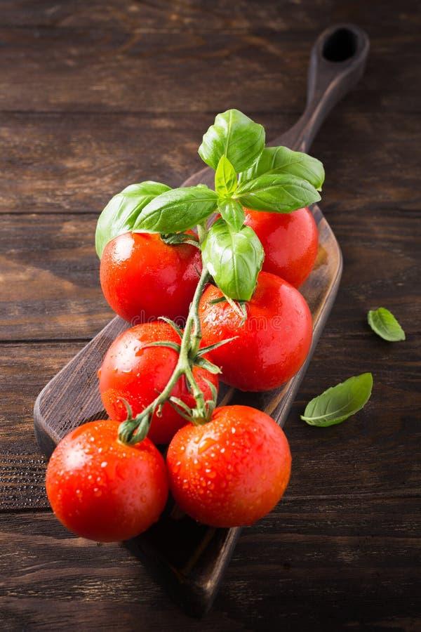 Tak van rijpe natuurlijke tomaten en basilicumbladeren royalty-vrije stock foto