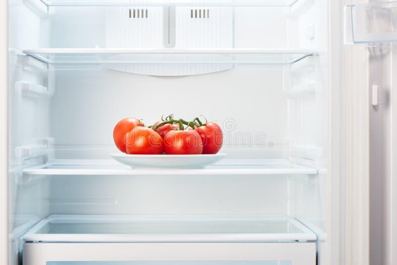 Tak van rode tomaten op witte plaat in open lege ijskast stock fotografie