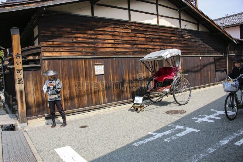 TAKAYAMA JAPAN - MARS 27, 2019: Vagn och rickshaw för handelsresanden som går på de gamla gatorna Takayama, Gifu prefektur, Japan royaltyfri bild
