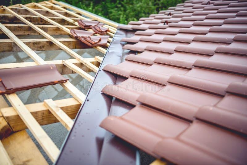 Takbyggnad på konstruktion för nytt hus Bruna taktegelplattor som täcker godset fotografering för bildbyråer