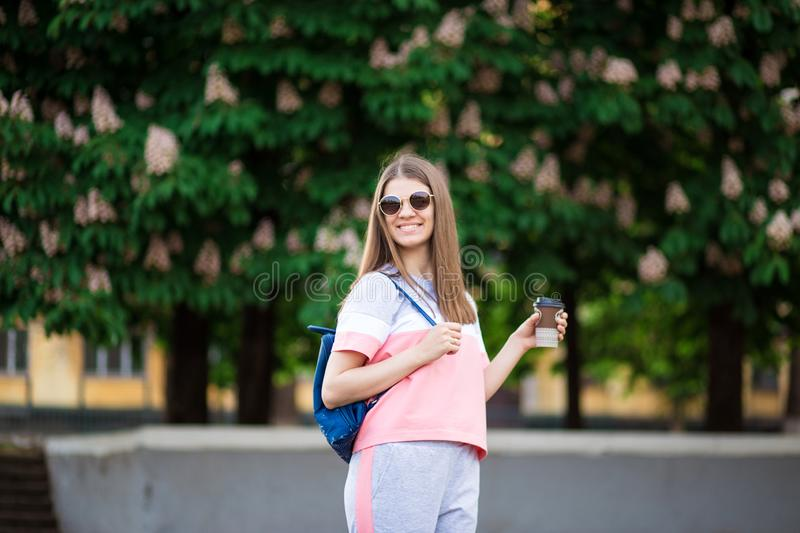 Take away coffee. Beautiful girl in sunglasses with backpack walk by summer street with coffee. stock image